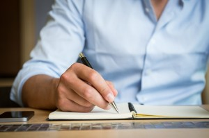Man taking down note in diary